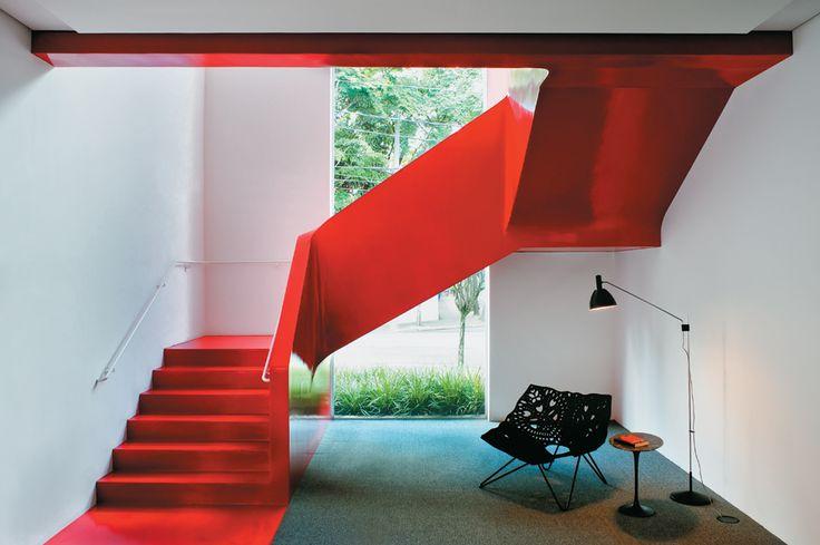 """. a solução do arquiteto Gustavo Horta foi retirar o revestimento antigo e propor uma nova cobertura ao conjunto. Sobre a estrutura de alvenaria e concreto, Gustavo aplicou um tipo de resina plástica fácil de limpar e de efeito lúdico, o Resinfloor, na cor vermelha. """"a escada se tornou assim uma fita vermelha solta no espaço"""", descreve ele"""