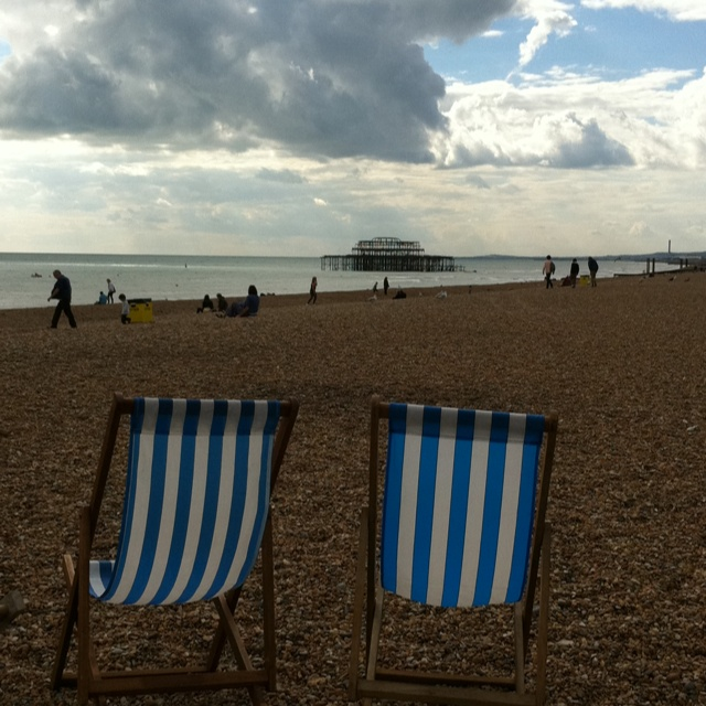 Empty deck chairs waiting for their next guests with a view of the burned down Pier in Brighton