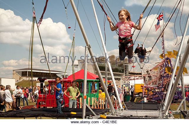 Young girl enjoying the trampoline, Newmarket Town Carnival, Suffolk UK - Stock Image