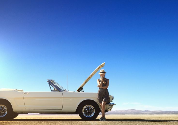 Caucasian woman stranded with broken down convertible on remote road - Caucasian…