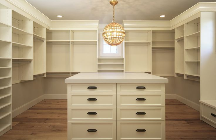 Cream walk-in closet features a French crystal sphere chandelier illuminating a cream closet ...