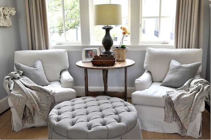 The round ottoman is tufted in a slightly darker linen.  On the chairs – the two pillows are a light gray blue which pulls out the color of the walls.  The curtains are yet another shade of linen.  Notice how in this one setting – four different shades of linen are used – which creates the interest and texture.    An antique wine table sits between them with a balustrade lamp.