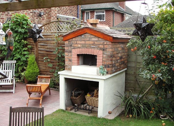 Outdoor Brick Pizza Ovens | Outdoor brick oven with roof, on a base of stucco over cement blocks.