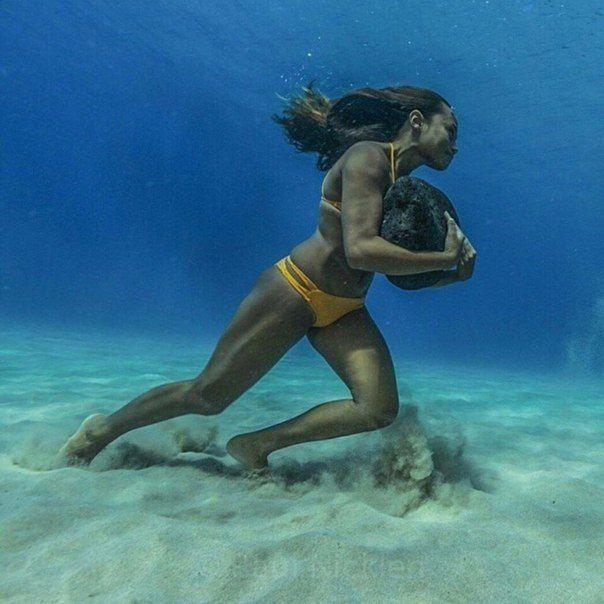 Тренировка выносливости у серфингистки. Она бегает по дну океана с 20-килограммовым камнем, для того чтобы иметь достаточно сил в противостоянии ударам волн.