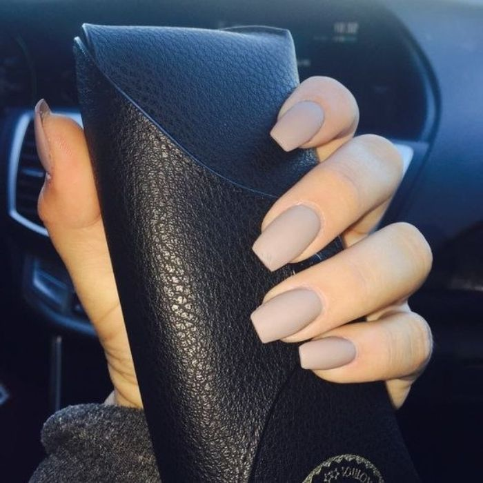greyish-beige matte nail polish, on a square manicure, worn by a hand, holding a…