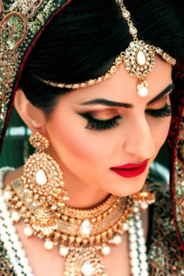 South Asian bridal makeup. Smokey eye with lashes and a red lip. Desi jewelry.