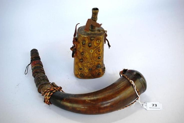 2 North African powder horns, one with studded brass & geometric patterns. The other with wooden base and top, painted red & black.