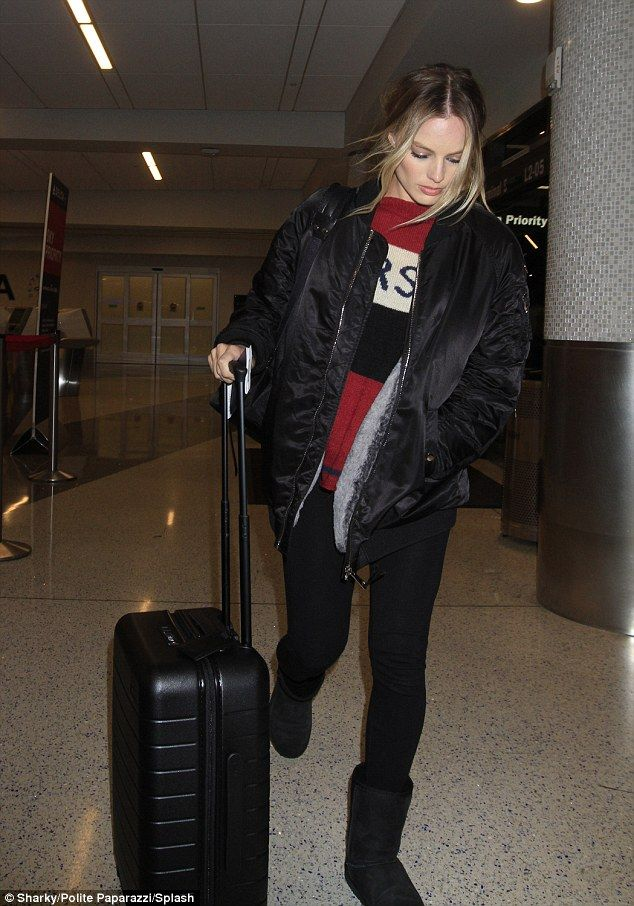 Flying solo: Newlywed Margot Robbie looked a little downcast as she flew out of LAX airport in Los Angeles on Tuesday