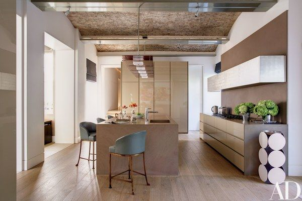 The garden-level kitchen's cabinetry is by Minotti Cucine, with a cooktop by Wolf and barstools by Sultana; the sculpture at right is by Nicole Wermers.
