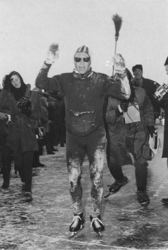 Reinier Paping als de winnaar van wedstrijdrijders van de 12e Elfstedentocht in 1963 bij het bereiken van de finish op de Grote Wielen in Leeuwarden