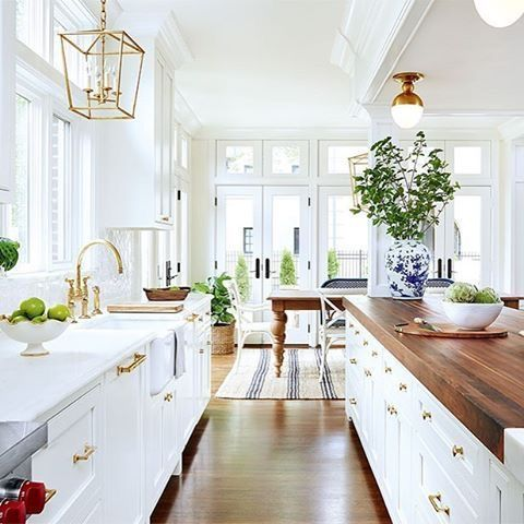 Bright white kitchen with wood counters and gold hardware. Simply gorgeous