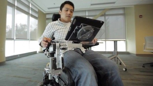 """A researcher at Purdue University has developed a motorized wheelchair tray that is designed to make it easier for wheelchair users to access mobile devices. Employing a motorized arm, the """"RoboDesk"""" can deploy or retract a tablet or lightweight laptop computer as needed."""