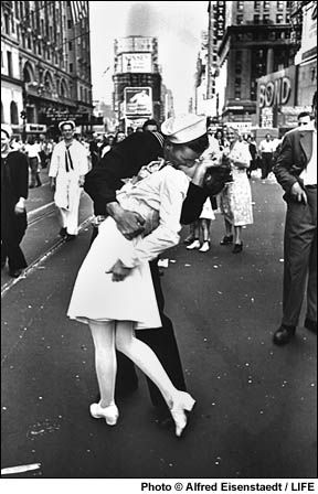 """V-J Day in Times Square, New York City, 1945, by Alfred Eisenstaedt for Life magazine, """"In Times Square on V.J. Day, I saw a sailor running along the street grabbing every girl in sight. I was running ahead of him with my Leica looking back over my shoulder. Then suddenly, in a flash, I saw something white being grabbed. I turned around and clicked the moment the sailor kissed the nurse...I took exactly four pictures. It was done within a few seconds."""""""