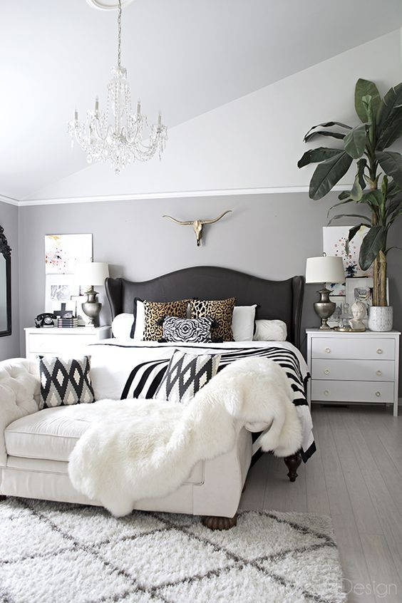 neutral bedroom with crystal chandelier, button tufted chaise, black and white accents and leather studded wingback bed - Cuckoo4Design
