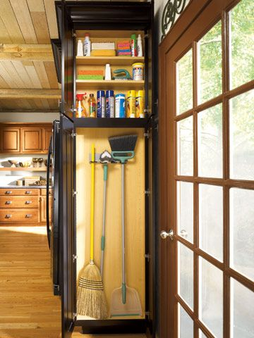 Kitchen storage for brooms and cleaning supplies built into end of cabinet
