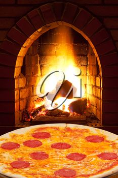 italian pizza with sausage and open fire in wood burning oven