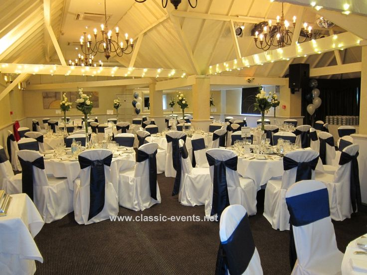 https://flic.kr/p/8zww93 | Classic Events at Rowhill Grange Navy | Wedding Venue Decor & Styling at Rowhill Grange Navy blue colour theme Beams swagged with fairy lights and organza Pleated & tailored chair covers with navy blue taffeta sash Tall vases filled with bouquets of roses & lisianthus Napkins dressed with ribbons & diamante buckles www.classic-events.net