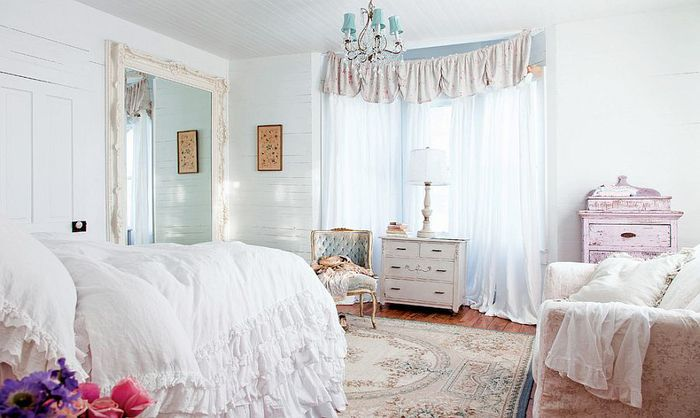 frilly white covers, on a big fluffy bed, near pale patterned, shabby chic sofa, and other vintage furniture