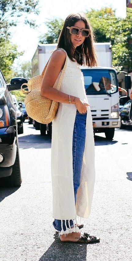 Natasha Goldenberg with vintage jeans, a long tassled top, black slides and a basket bag