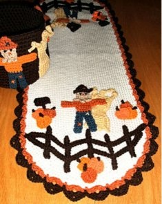 Decorate your table for Fall with the pretty seasonal table runner and bucket. The scarecrow has been put in charge of the pumpkin patch this year. He's stands against a haystack behind a split rail fence and has piles of pumpkins all around him. The bucket is decorated with scarecrows and haystacks and will look so pretty with either Fall colored napkins in it or even little pumpkins and gourds. They are made from worsted weight yarn.