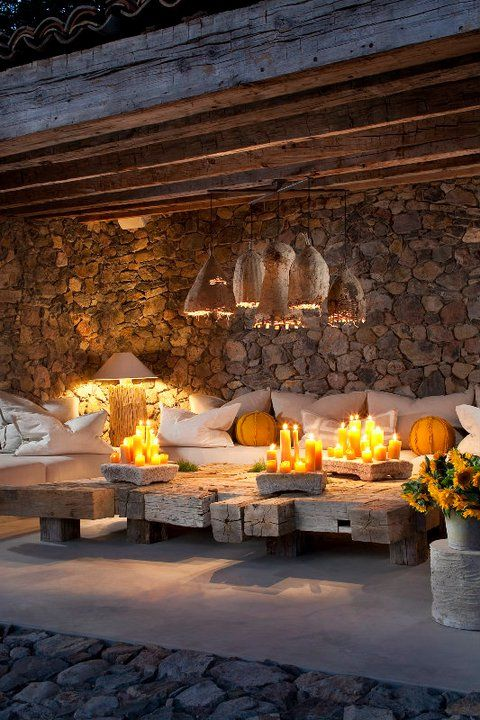 One of the beautiful outdoor lounging areas. Love the splash of yellow and the coffee table constructed of old beams.