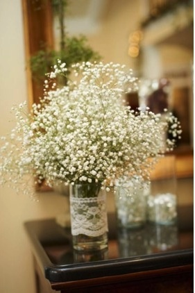 Simple baby's breath bouquet in a lace-wrapped jar.