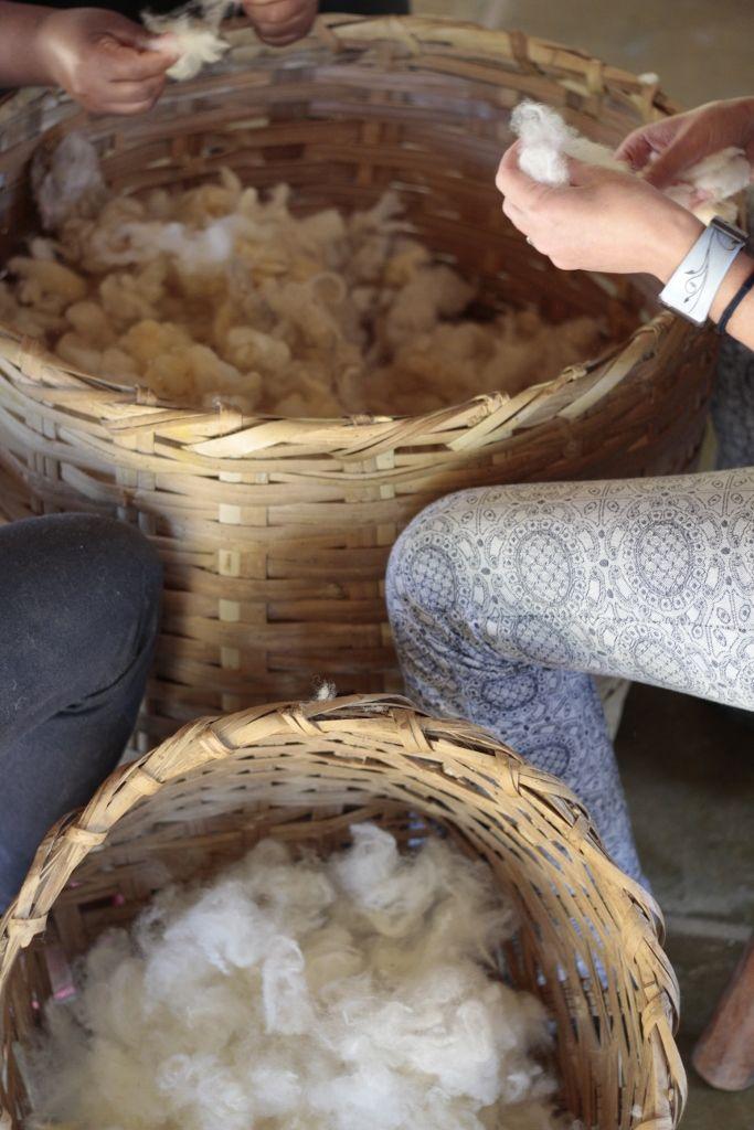 Transformamos a lã compacta em tufos bem soltos e macios, a lã fica mais solta e disposta em pequenas mechas, com o cesto cheio de lã pronta para ser cardada.