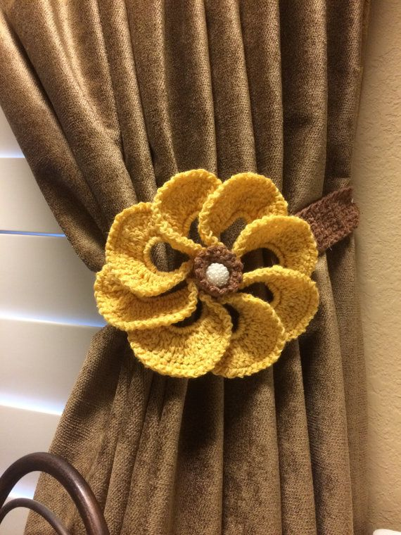 Homemade crochet curtain tieback. Flower is a light yellowish gold color. The flower Has a pearl center. Flower measures 6 1/2 inches and the band is brown and measures 22 inches long. Neutral color compliments any decor style.