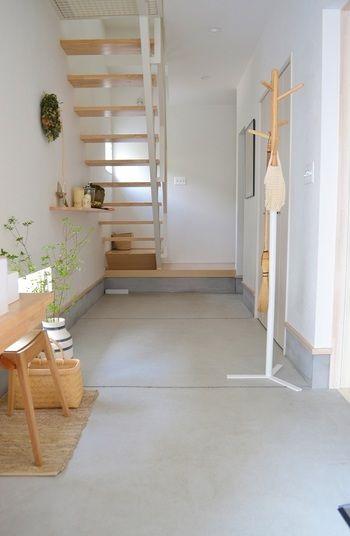 白とライトグレーのクリーンな空間に、白木と緑がやさしい印象を添える土間。階段下には季節によってモビールを吊ったり、ツリーを置いたりと演出を楽しんでいるそうです。