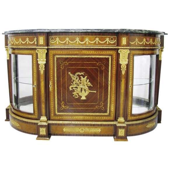 Dunquerque - vitrine estilo Napoleão III, em madeira com marqueterie. Laterais arredondadas com vidro e porta central. Tampo com mármore verde rajado. Ricas guarnições em bronze dourado. Med. 104x185x59cm.