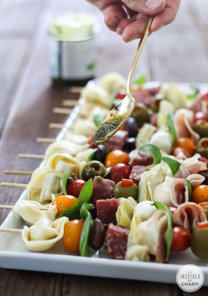 Antipasto Kabobs | Inspired by Charm  Here's what you will need:  cherry tomatoes tortellini, cooked and cooled olives, kalamata and green salami, cubed prosciutto, sliced sharp cheddar cheese, cubed basil leaves basil pesto wood skewers  Skewer the above ingredients onto wood skewers; then drizzle with basil pesto