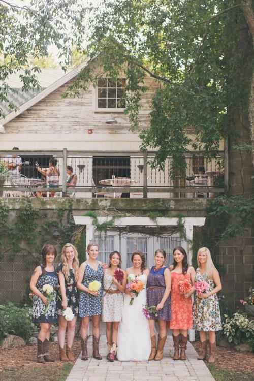 A country wedding: flower dresses for the bridesmaids, cowboy boots, and a barn.