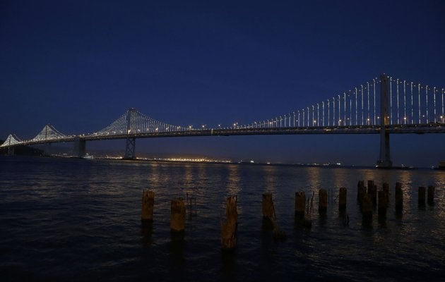The San Francisco-Oakland Bay Bridge has been turned into the latest, and by far the biggest, backdrop for New York artist Leo Villareal, who has individually programmed 25,000 white lights spaced a foot apart on 300 of the span's vertical cables to create what is being billed as the world's largest illuminated sculpture. (AP Photo/Jeff Chiu)