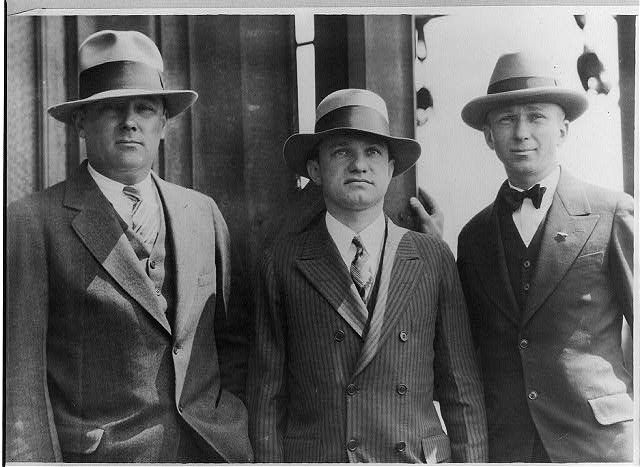 This photo from the 1920s shows three men wearing suit jackets and fedoras, which middle-class men tended to wear. The man in the middle is wearing a pinstriped, a common pattern, double-breasted suit jacket. All three of them are wearing short suit jackets which men wore instead of the old, long jackets.