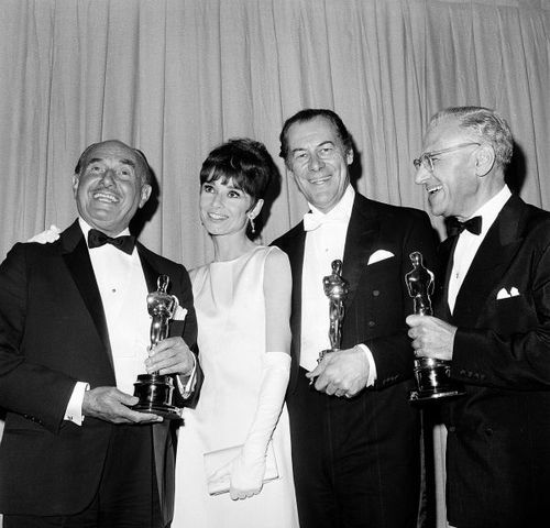 Jack Warner with his Oscar for Best Picture, Audrey Hepburn, Rex Harrison with his award for Best Actor and George Cukor holding his Oscar for Best Director. All for My Fair Lady. 37th Academy Awards, April 5, 1965.