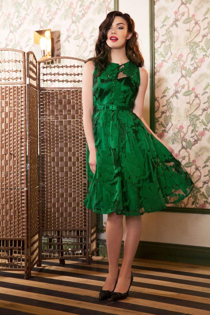 """De50s Maggie Goddess Swing Dressis eenclassy feestjurk gehuld in groen, oh la la!  Dit prachtige smaragdgroene jurkje is geïnspireerd op een jurk van de lovely Dita von Teese, heeft een mooie hartvormige halslijn en is bedekt met doorzichtig gebloemd chiffon voor een adembenemend mooi effect! De aansluitende top heeft een """"faux"""" knopenrij, een elegante riem en loopt uit in een zwierige semi-swing rok met platte plooitjes. Uitgevoerd in een gebloemd chiffon stofje (stre..."""