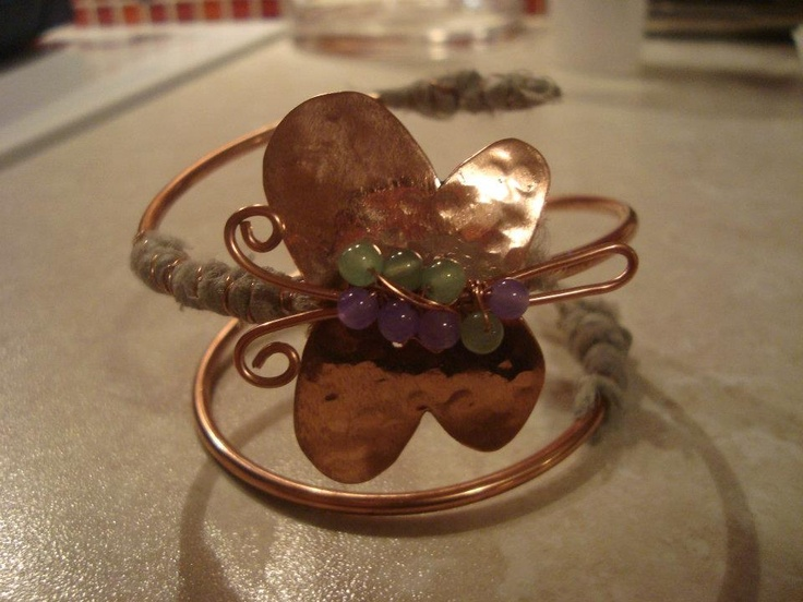 Cooper wire bracelet with cooper hammered butterfly decorated with beads and silk fabric.