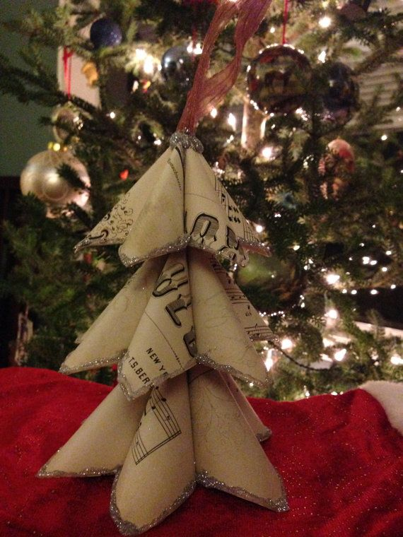 Christmas tree made from vintage sheet music with the tips lined in silver glitter