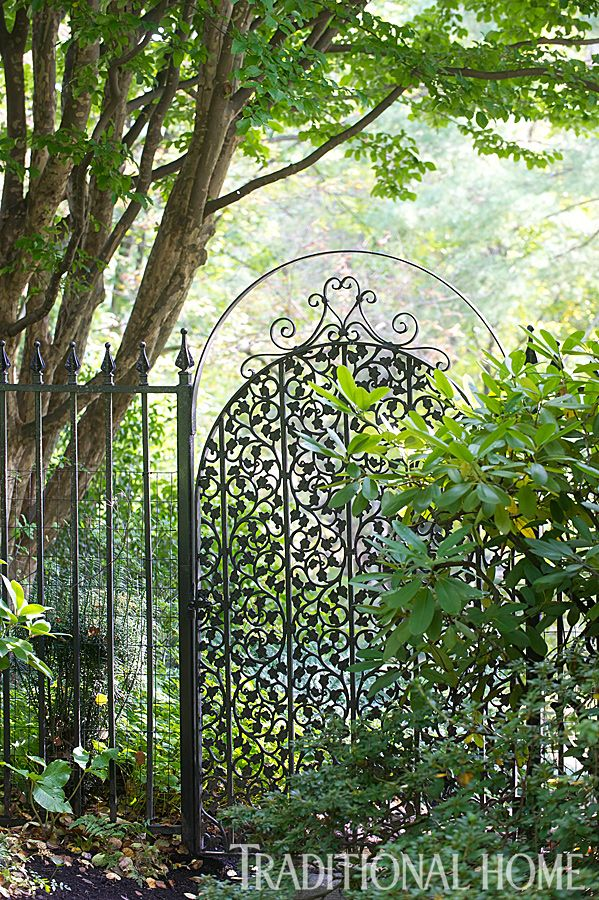 A lovely iron garden gate is shrouded by greenery. - Photo: Rob Cardillo
