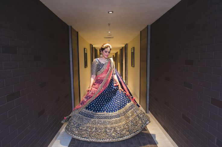 A Royal Blue Lehenga with heavy Gold work paired with a coral Dupatta by Om Prakash Jawahar of Bride Riddhi of WeddingSutra. Photo Courtesy- Deep Panchal'S Photography  #WeddingSutraP2W