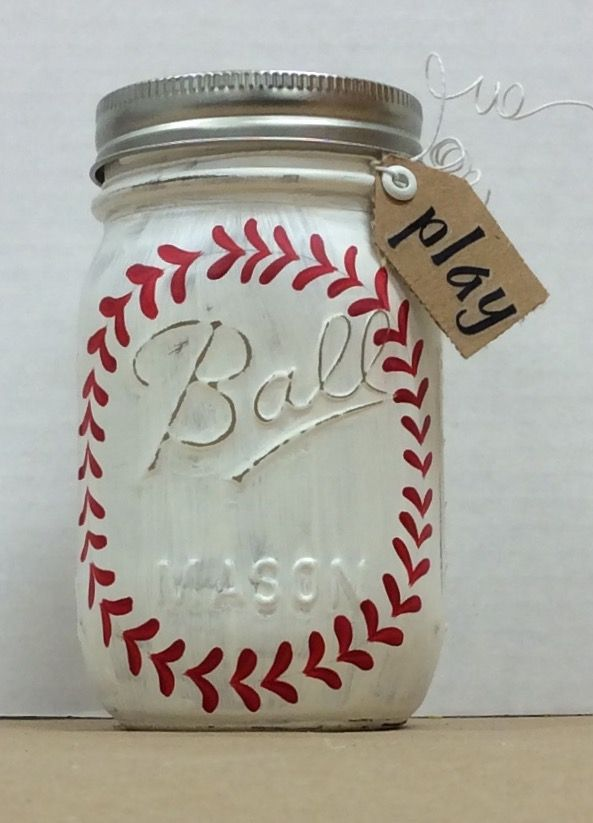 """Baseball Painted Mason Jar.  Used Folk Art Chalk paint, added details with small brush and F/A enamel paint, dried, sanded, sealed with spray acrylic sealer.  For detail work, used pencil to add a circle as a guide for stitching, 1 on each side of jar. Covered lid with burlap inside rim.  Used wire to attach a small tag that says """"play"""".  Tag has eyelet, word added with stickers."""