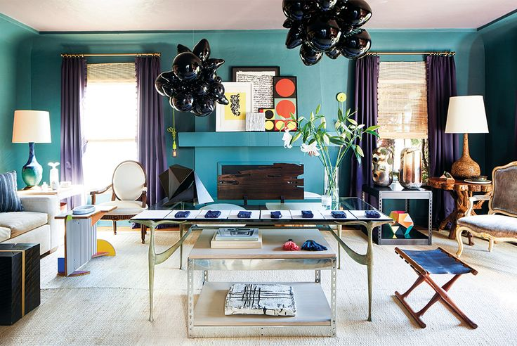 In the eclectic salon, painted in a custom blue-green shade using Benjamin Moore colors, a pair of suspended sculptures by Elyse Graham serve as a dramatic focal point.