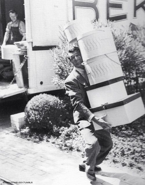 Cary Grant carrying Hedda Hopper's hat boxes into her new home - what a fabulous picture!
