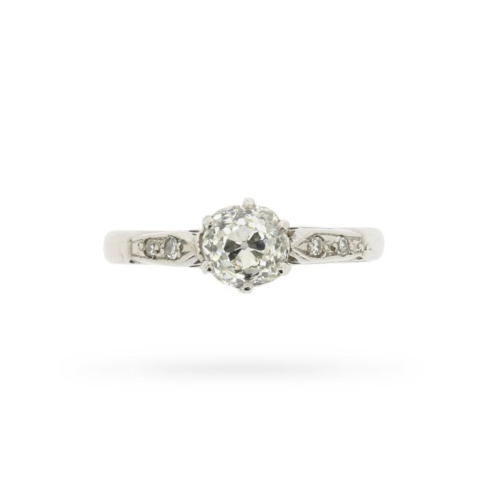 This original Art Deco era engagement ring presents an old cut diamond within its original handmade, platinum, six claw cathedral setting. A pair of eight cut diamonds mounted in grain settings shimmers at each of the ring's raised, chenier-supported shoulders, and a pierced gallery puts the finishing unique touches to this elegant circa 1920s period piece.