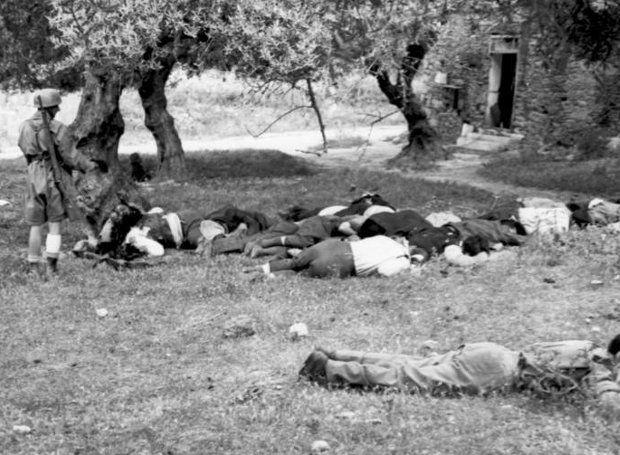 """ΝΕΚΡΟΙ ΚΕΙΤΟΝΤΑΙ ΠΙΑ ΟΙ 25 ΗΡΩΕΣ ΣΤΟ ΚΟΝΤΟΜΑΡΙ ΤΗΣ ΚΡΗΤΗΣ. Ύστερα από τη χαριστική βολή τους κοιτάει αδιάφορα ένας από τους στυγνούς δολοφόνους που """"έμεινε"""" φρουρός των πτωμάτων. Ένα ακόμα ανοσιούργημα συντελέστηκε το 1941. Ύστερα από τους βομβαρδισμούς των αμάχων στις πόλεις της Ευρώπης -όπου εισέβαλε η χιτλερική Γερμανία- ακολούθησαν οι τουφεκισμοί των ομήρων και των αθώων πολιτών..."""