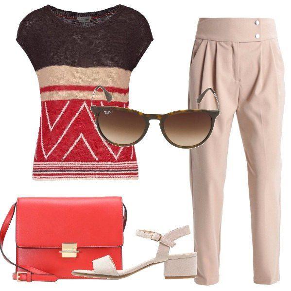 L'outfit è composto da una maglia a fantasia ed un paio di pantaloni beige a vita alta. Il look si completa con un paio di sandali dal tacco medio, una borsa a tracolla rossa ed un paio di occhiali da sole Ray-Ban.