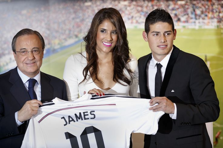Real Madrid president Florentino Perez, left, and new Real Madrid player James Rodriguez, from Colombia, right, accompanied by his wife Daniela Ospina, pose for photographers holding his new shirt during his official presentation at the Santiago Bernabeu stadium in Madrid, Spain, Tuesday, July 22, 2014, after signing for Real Madrid. Real Madrid have signed Rodriguez from Monaco on a six-year contract, (AP Photo/Daniel Ochoa de Olza)