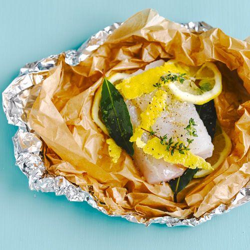 Steek de barbecue aan.    Leg een stukbakpapier op een dubbele laag alufolie.Leg er 2 schijfjes citroen, het laurierblaadjeen dan de vis, de rest van de citroen, decitroenrasp en kruiden in. Sprenkel er watolie over,...