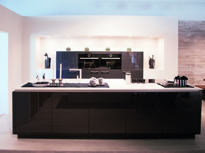 Hoogglans zwart-wit keuken.  Deze hoogglans keuken zorgt door het gebruik van zwart en wit voor een contrasterend effect. Het kookeiland is voorzien van greeploze kasten, een kookplaat en gootsteen. Met de halfhoge kolomkasten als middelpunt van de muur krijgt de gehele keuken een mooie symmetrische vorm.