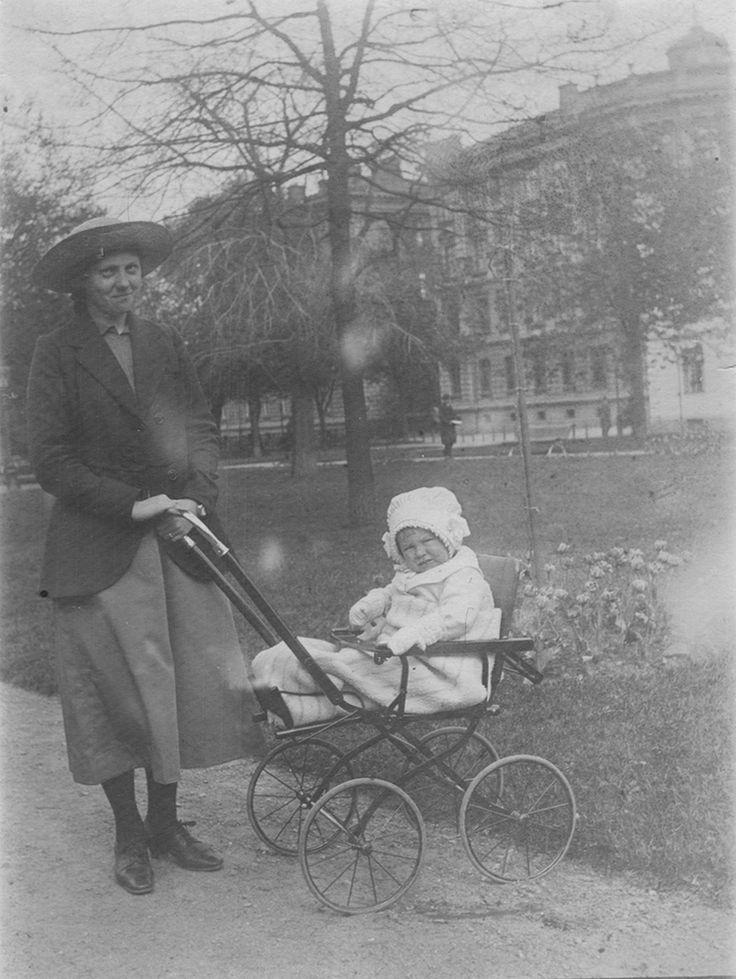 Bilden visar Gurly Axelsson (gift Johansson) som är ute och går med ett barn i barnvagn. Hon arbetade antagligen som barnflicka åt någon familj vid tillfället. De befinner sig i Järnvägsparken.  Gurly Axelsson är Birgit Pehrssons adoptivmor.